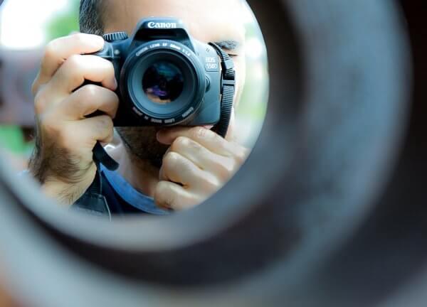 Man holding camera looking through a metal pipe