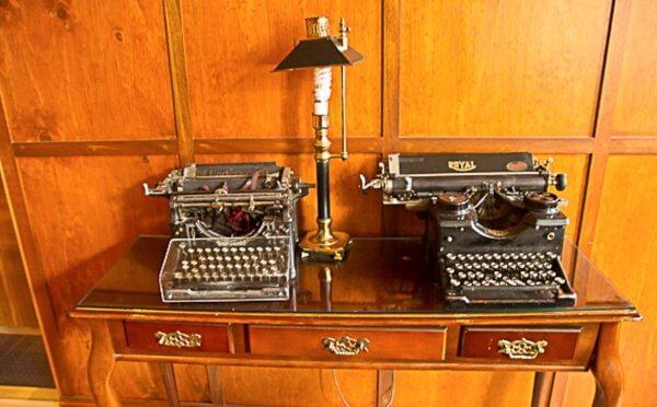 Two antique typewriters and an old lamp
